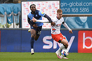 Wycombe Wanderers midfielder Fred Onyedinma (23) battles for possession with Luton Town defender James Bree (26) during the EFL Sky Bet Championship match between Wycombe Wanderers and Luton Town at Adams Park, High Wycombe, England on 10 April 2021.