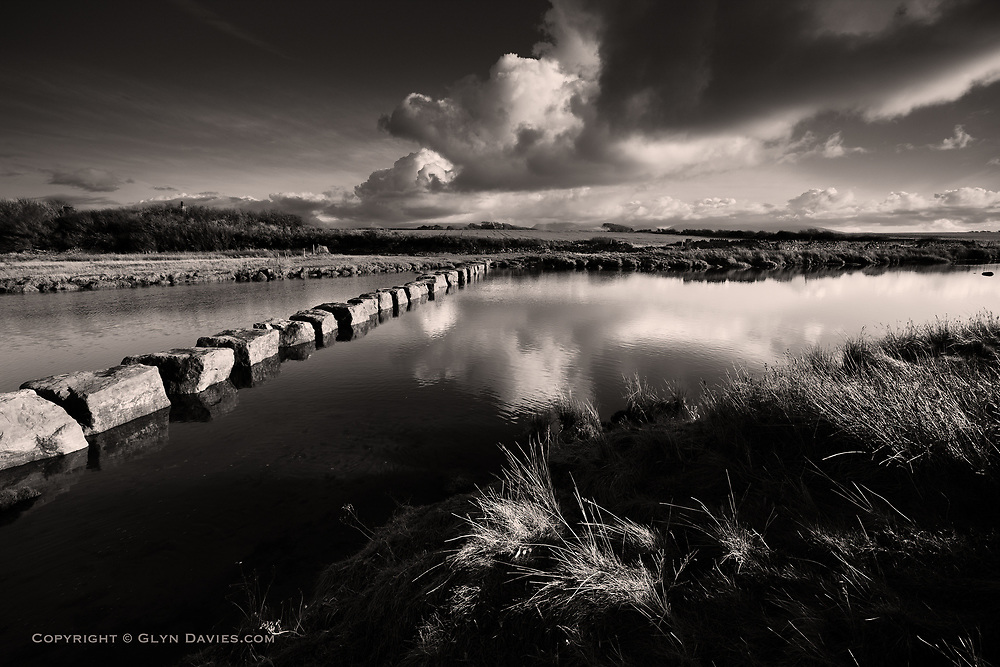 Dramatic large cumulonimbus clouds increased over lush rolling hillsides and farmland, whilst the ancient stepping stones navigate the walker across the wide gap of the Afon Braint River near Newborough on West Anglesey. The hills of Snowdonia can just be seen in the distance,