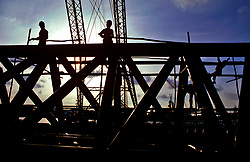 Stock photo of a silhouette of two men working on an oil rig