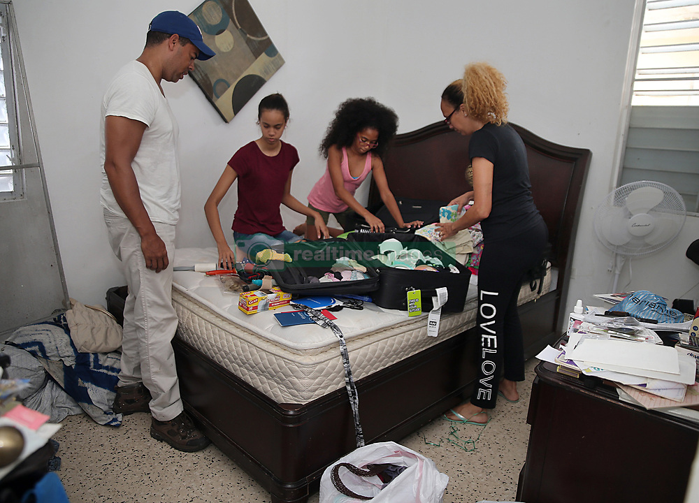 Carlos Rolâ¤â€n, a financial planner from the town of San Lorenzo, his wife Nerys Medina and their daughters Glennys (second from left) and Karelys, sort out through their damages personal items in the master bedroom of their home as they package to leave Puerto Rico on October 2. After deciding against their will to leave since their house got damaged, he is jobless and their daughters' schools are closed for an unknown amount of time forcing many Puerto Ricans to fly to the U.S. after Hurricane Maria, (category 4) passed through Puerto Rico devastating the island leaving residents without power and ways to communicate on Sept. 20. on October 02, 2017. Photo by Pedro Portal/Miami Herald/TNS/ABACAPRESS.COM