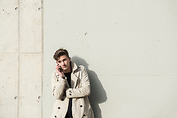 Young man talking on mobile phone and leaning against concrete wall, Munich, Bavaria, Germany