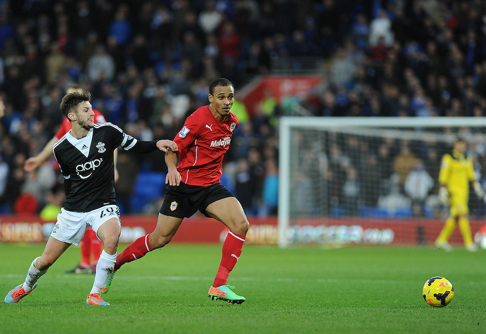 Southampton's Adam Lallana battles with Cardiff City's Peter Odemwingie<br /> <br /> Photo by Ashley Crowden/CameraSport<br /> <br /> Football - Barclays Premiership - Cardiff City v Southampton - Thursday 26th December 2013 - Cardiff City Stadium - Cardiff<br /> <br /> © CameraSport - 43 Linden Ave. Countesthorpe. Leicester. England. LE8 5PG - Tel: +44 (0) 116 277 4147 - admin@camerasport.com - www.camerasport.com