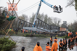 HS2 security guards form a line across the River Colne in front of Dan Hooper, widely known as Swampy during the 1990s, and a large cherry picker containing bailiffs on 8th December 2020 in Denham, United Kingdom. The climate and roads activist had occupied a bamboo tripod positioned in the river the previous day in order to delay the building of a bridge as part of works for the controversial HS2 high-speed rail link and a large security operation involving officers from at least three police forces, National Eviction Team enforcement agents and HS2 security guards was put in place to facilitate his removal.