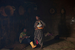 Fifteen-year-old Destaye and her husband Addisu, 27, are seen inside their home with their son near Bahir Dar, Ethiopia on Aug. 10, 2012. They divide their time between working in the fields and taking care of their 6-month-old baby. Like many other young couples, they tend to the domestic, economic and personal demands of being young parents. At the time of their marriage, when Destaye was age 11, she was still in school and her husband expressed interest in letting her continue her education. Since the birth of their son, however, she has had to confine her life exclusively to being a wife and mother.