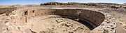 Casa Rinconada, occupied about AD 1140-1200, is an isolated great kiva (out of four in Chaco Canyon), built 63 feet (19 m) in diameter with a circular inner bench, masonry firebox, masonry vaults, 34 niches, four large pits for seating roof supports, plus an unusual 39-foot (12 m) passage dug underground through sandstone and shale. Chaco Culture National Historical Park hosts the densest and most exceptional concentration of pueblos in the American Southwest and is a UNESCO World Heritage Site. Chaco Canyon is in remote northwestern New Mexico, between Albuquerque and Farmington, USA. From 850 AD to 1250 AD, Chaco Canyon advanced then declined as a major center of culture for the Ancient Pueblo Peoples. Chacoans quarried sandstone blocks and hauled timber from great distances, assembling fifteen major complexes that remained the largest buildings in North America until the 1800s. Climate change may have led to its abandonment, beginning with a 50-year drought starting in 1130. This panorama was stitched from 5 overlapping photos.