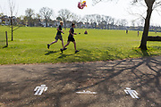 On the first day of the Easter Bank Holiday weekend, and at the end of the second week of lockdown restrictions by the UK government, runners use their daily exercise entitlement to spend a warm afternoon near a stencil for keeping 2 metres apart in Ruskin Park in a public green space in the borough of Lambeth, on 10th April 2020, in London, England.