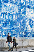 Couple passing azulejos Portuguese blue and white wall tiles Capela das Almas de Santa Catarina  - St Catherine's Chapel in Porto, Portugal