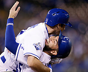 Kansas City Royals Billy Burns, top, celebrates his game-winning sacrifice fly ball with Eric Hosmer, bottom, in the 11th inning of a baseball game against the Minnesota Twins at Kauffman Stadium in Kansas City, Mo., Tuesday, Sept. 27, 2016. (AP Photo/Colin E. Braley)