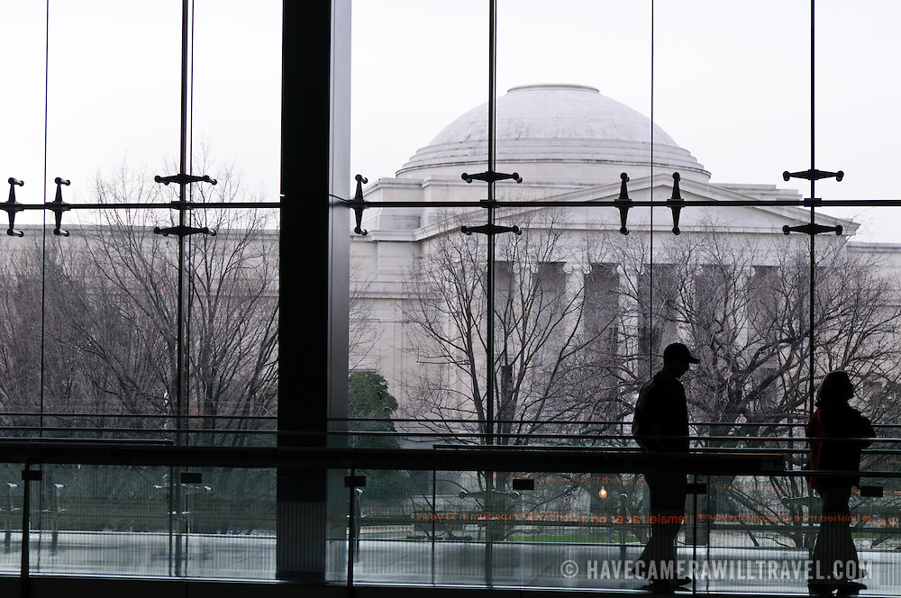 The National Gallery of Art building as seen through the glass panels of the Newseum across the street. The Newseum is a 7-story, privately funded museum dedicated to journalism and news. It opened at its current location on Pennsylvania Avenue in April 2008.