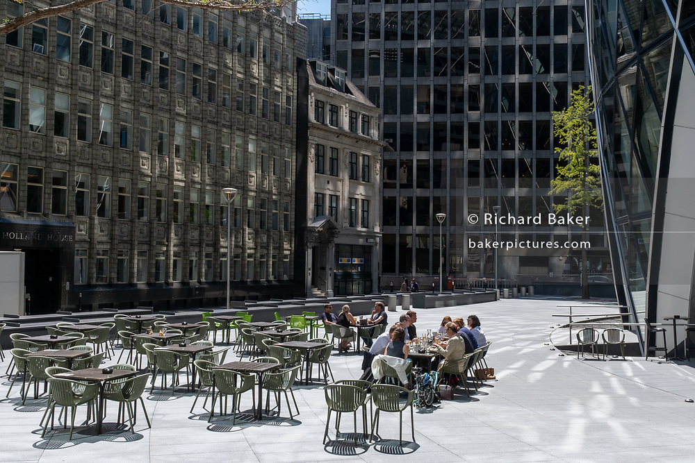 With thousands of employees in the capital's financial district still working from home during the Coronavirus pandemic, other City workers enjoy a socially distanced lunch beneath the Swiss Re building (aka the Gherkin), on 29th July 2020, in London, England.