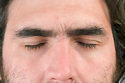 close up of a man's face with his eyes relaxed closed