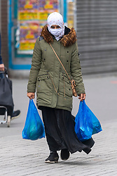 © Licensed to London News Pictures. 20/05/2021. London, UK. A woman wearing a face mask walk along Hounslow High Street, West London. Hounslow is the first London borough to actively test for the Indian Covid variant B.1.617.2. Photo credit: Ray Tang/LNP
