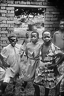 Girls playing and posing in the ruins of a village house - West Nile, Moyo District, Uganda.