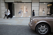 Exclusive clothes shop window of Chanel and a Rolls Royce car on New Bond Street in Mayfair, London, England, United Kingdom. Bond Street is one of the principal streets in the West End shopping district and is very upmarket. It has been a fashionable shopping street since the 18th century. The rich and wealthy shop here mostly for high end fashion and jewellery.