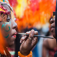 London, UK - 25 August 2014: a reveller has her make up done during the Notting Hill Carnival in London.