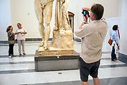 A man takes a photograph of a statue in the National Archaeological Museum in Naples, Italy. The Museo Archeologico Nazionale di Napoli, MANN, formerly Real Museo Borbonico Bourbons Royal Museum is considered the most important Italian archaeological museum and one of the most important in the world for classical, and particularly ancient Roman, archaeology. Its collection includes works of the highest quality produced in Greek, Roman and Renaissance times and especially Roman artifacts from nearby Pompeii, Stabiae and Herculaneum.