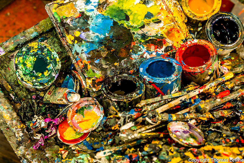 Small used paint cans in artist studio for painting small wood objects
