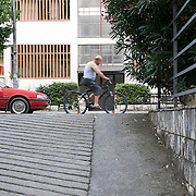 MOSTAR, BOSNIA AND HERZEGOVINA - JUNE 26:  A man riding its bike passes in front of the Hero Hotel garage exit ramp on  June 26, 2013 in Mostar, Bosnia and Herzegovina.The Siege of Mostar reached its peak and more cruent time during 1993. Initially, it involved the Croatian Defence Council (HVO) and the 4th Corps of the ARBiH fighting against the Yugoslav People's Army (JNA) later Croats and Muslim Bosnian began to fight amongst each other, it ended with Bosnia and Herzegovina declaring independence from Yugoslavia.  (Photo by Marco Secchi/Getty Images)