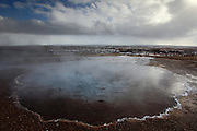 Clouds are reflected in a blue steaming geothermal pool at Geysir, South-West Iceland
