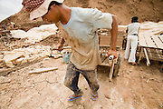 30 JUNE 2006 - PHNOM PENH, CAMBODIA: A worker hauls a load of wet bricks to a patio to dry them before they go into a kiln. According the United Nations Food and Agricultural Organization, there are more than 70 brick factories in Phnom Penh and its environs. Environmentalists are concerned that the factories, most of which burn wood in their kilns, contribute to deforestation in Cambodia. They are encouraging factory owners to switch to burning rice husks, as brick kilns in neighboring Vietnam do. The brick factories are kept busy feeding Phnom Penh's nearly insatiable appetite for building materials as the city is in the midst of a building boom brought by on economic development and the need for new office complexes and tourist hotels.   Photo by Jack Kurtz / ZUMA Press