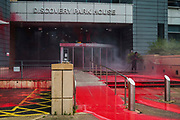 A man uses a pressure hose to wash red paint from the entrance to Discovery Park House after it was occupied and sprayed by Palestine Action activists in protest against the presence in Discovery Park of an Instro Precision factory on 4th October 2021 in Sandwich, United Kingdom. Instro Precision is a subsidiary of Israels largest publicly-traded arms company Elbit Systems supplying high precision military equipment and Palestine Action contends that Instro Precision equipment has been used by the Israeli military against the population of Gaza.