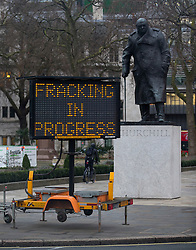 Licensed to London News Pictures. 09/02/2016. London, UK. A false road warning sign put up on the edge of Parliament Square says 'Fracking in progress' . Members of Greenpeace have installed a 10 metre life-like fracking rig and drill on Parliament Square in London. The rig emits a flame created using bio ethanol. The protest coincides with the first day of the independent Planning Inspectorate inquiry into whether fracking will go ahead in Lancashire. Photo credit: Peter Macdiarmid/LNP