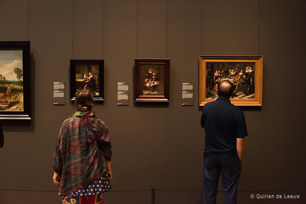 Bezoekers van het Rijksmuseum bekijken schilderijen uit de Gouden Eeuw collectie