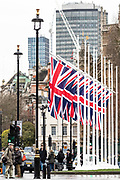 """January 30, 2020, London, England, United Kingdom: People walk beside the British Union flags outside Parliament near the statue of Winston Churchill in London, Thursday, Jan. 30, 2020. Although Britain formally leaves the European Union on Jan. 31, little will change until the end of the year. Britain will still adhere to the four freedoms of the tariff-free single market """" free movement of goods, services, capital and people. (Credit Image: © Vedat Xhymshiti/ZUMA Wire)"""