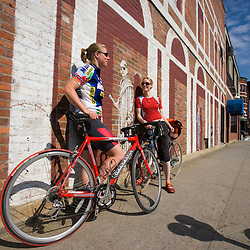 Two young women take a break from biking on Railroad Street in St. Johnsbury.Vermont...Two young women take a break from biking on Railroad Street in St. JohnsburyVermont. (MR)
