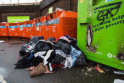 London, December 31 2017. Rubbish and old clothes mount up at some recycling sites in London, with others appearing to have had their contents recently collected. PICTURED: Some fly-tipping appears to have taken place at the community recycling centre at Ladbroke Grove in West London. © SWNS