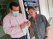 Apr. 27, 2009 -- NOGALES, SONORA, MEXICO: Alejandro Mercado, a dentist in Nogales, Sonora, Mexico, wears a surgical mask while he prepares one for a friend. Both men decided to wear the masks to protect them from the swine flu.  The Mexican government broadened its efforts to control the outbreak of swine flu Monday closing schools throughout the country. In Nogales, on Mexico's northern border with the US, people started wearing masks as news of the outbreak spread.  Photo by Jack Kurtz