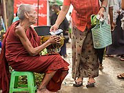 08 NOVEMBER 2014 - SITTWE, RAKHINE, MYANMAR:  A Burmese woman drops money into the alms bowl of Buddhist monk at the entrance to the market in Sittwe. Sittwe is a small town in the Myanmar state of Rakhine, on the Bay of Bengal.  PHOTO BY JACK KURTZ