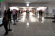People wait in line to enter the Apple Store at the Glendale Galleria indoor shopping mall, Friday, Dec. 4, 2020, in Glendale, Calif.