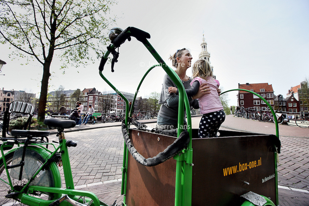 Nederland, Amsterdam , 28 april 2010..Moeder en kind op de bakfiets in centrum Amsterdam..Uit onderzoek blijkt dat meer moeders kiezen voor een woon werk situatie in het centrum van de stad om zodoende de afstand werk kind te verkleinen...Foto:Jean-Pierre Jans