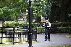 © Licensed to London News Pictures. 22/07/2016. LONDON, UK.  A police officer walks inside West Ham Lane Recreational Ground, known as Stratford Park on West Ham Lane in Stratford, where a man in his 20's was stabbed and killed yesterday afternoon. Two men were arrested nearby on suspicion of murder and taken into custody at an east London police station. Photo credit: Vickie Flores/LNP