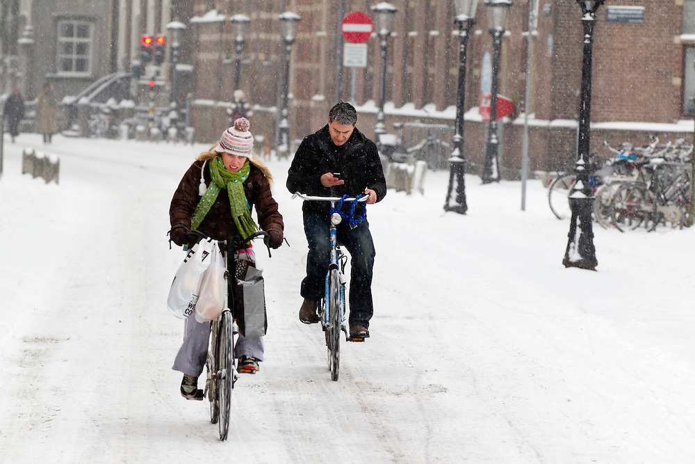 Met de volle tassen aan het stuur rijdt een meisje op de fiets door de sneeuw in Utrecht. Een jongen verstuurt ondertussen al fietsend een SMS.<br /> <br /> With bags full of shoppings a woman is cycling in the snow in Utrecht, while a man is sending text messages.