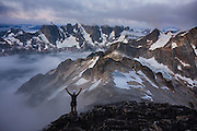 JIm Prager celebrates the dramatic view of the Picket Range from Luna Peak, North Cascades National Park, Washington. The view from the summit of Luna Peak is considered by those who have ventured there the most spectacular scenery of the Cascade Range.