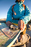 Young woman looking at compass and map while hiking in Yosemite National Park.