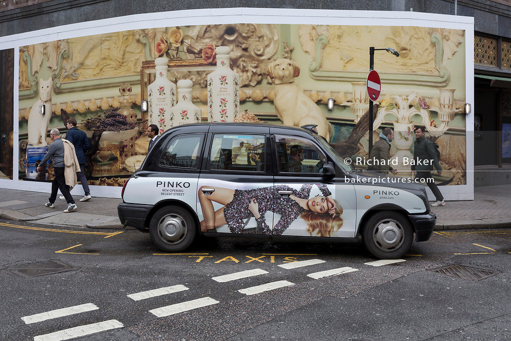 A taxi awaits a fare outside the temporary hoardings on the exterior of Harrods in Knightsbridge, on 8th April 2019, in London, England.