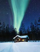 The Aurora Borealis over a log cabin in Lemmenjoki National Park, Lapland, Finland.