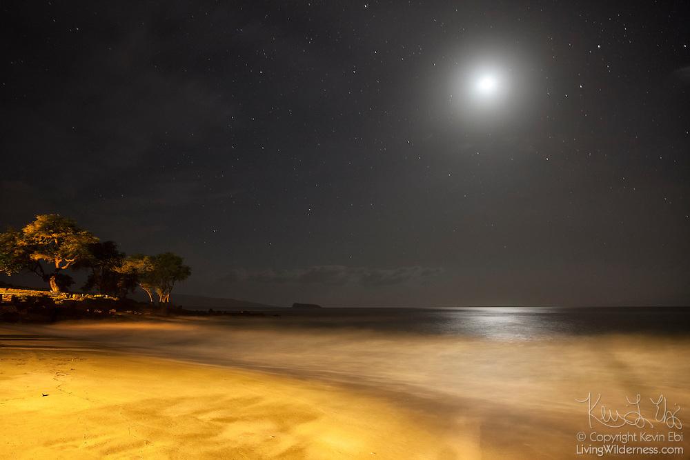 The moon shines over the golden Makena Beach on the Hawaiian island of Maui at night.