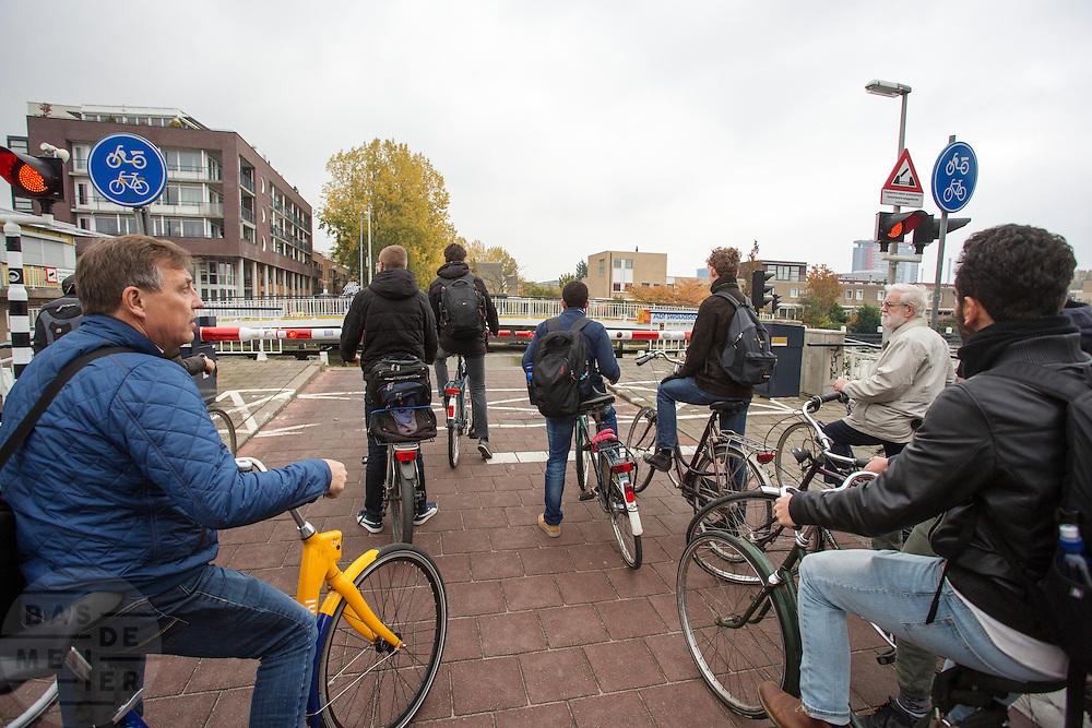 In Delft wachten fietsers bij een openstaande brug.<br /> <br /> In Delft cyclists wait for a bridge.