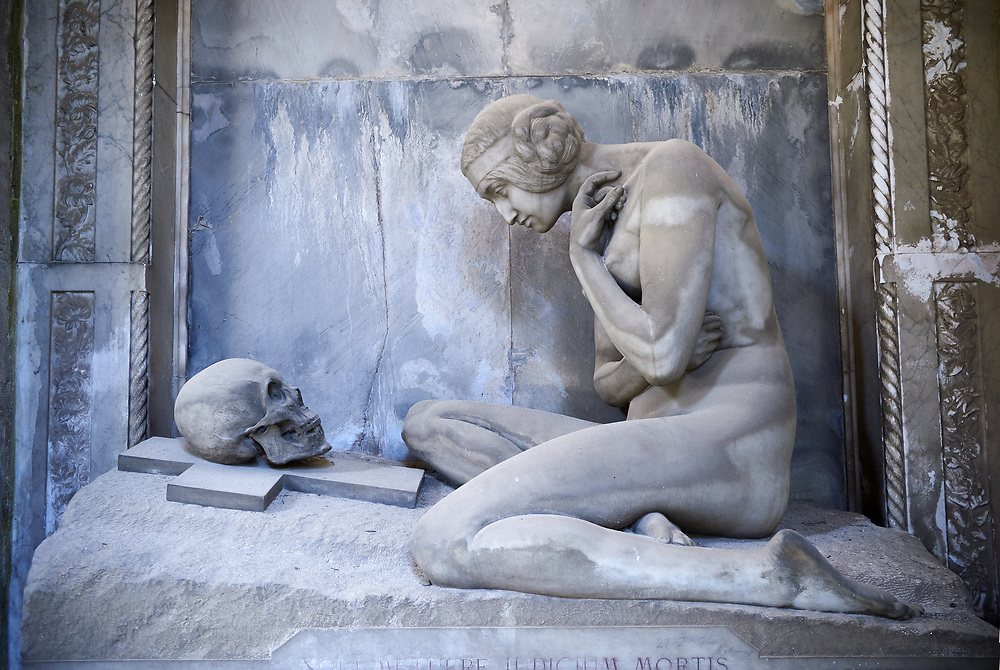 Picture and image of the stone sculpture of a nude looking at a skull on a crucifix.  Sculpted in an art Nouveau style the sculture is a reminder that beauty and life is transient. The Lavarello tomb sculpted by Demetrio Paernio 1914. The monumental tombs of the Staglieno Monumental Cemetery, Genoa, Italy .<br /> <br /> Visit our ITALY PHOTO COLLECTION for more   photos of Italy to download or buy as prints https://funkystock.photoshelter.com/gallery-collection/2b-Pictures-Images-of-Italy-Photos-of-Italian-Historic-Landmark-Sites/C0000qxA2zGFjd_k<br /> If you prefer to buy from our ALAMY PHOTO LIBRARY  Collection visit : https://www.alamy.com/portfolio/paul-williams-funkystock/camposanto-di-staglieno-cemetery-genoa.html
