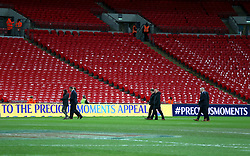 Officials inspect the pitch prior to the match