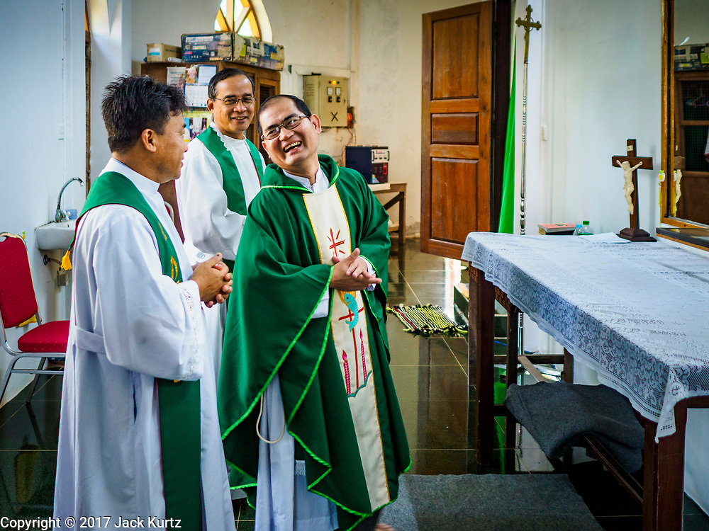 19 NOVEMBER 2017 - HWAMBI, YANGON REGION, MYANMAR: Fathers JOHN LEE (left, back to camera), JEROME KYI (center) and NOEL LATT prepare to celebrate mass at Sacred Heart's Catholic Church in Hwambi, about 90 minutes north of Yangon. Catholics in Myanmar are preparing for the visit of Pope Francis. He is coming to the Buddhist majority country November 27-30. There about 500,000 Catholics in Myanmar, about 1% of the population. Catholicism was originally brought to what is now Myanmar more than 500 years ago by Portuguese missionaries and traders.    PHOTO BY JACK KURTZ