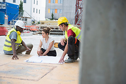 Architect reviewing blueprint with construction workers at building site, Munich, Bavaria, Germany