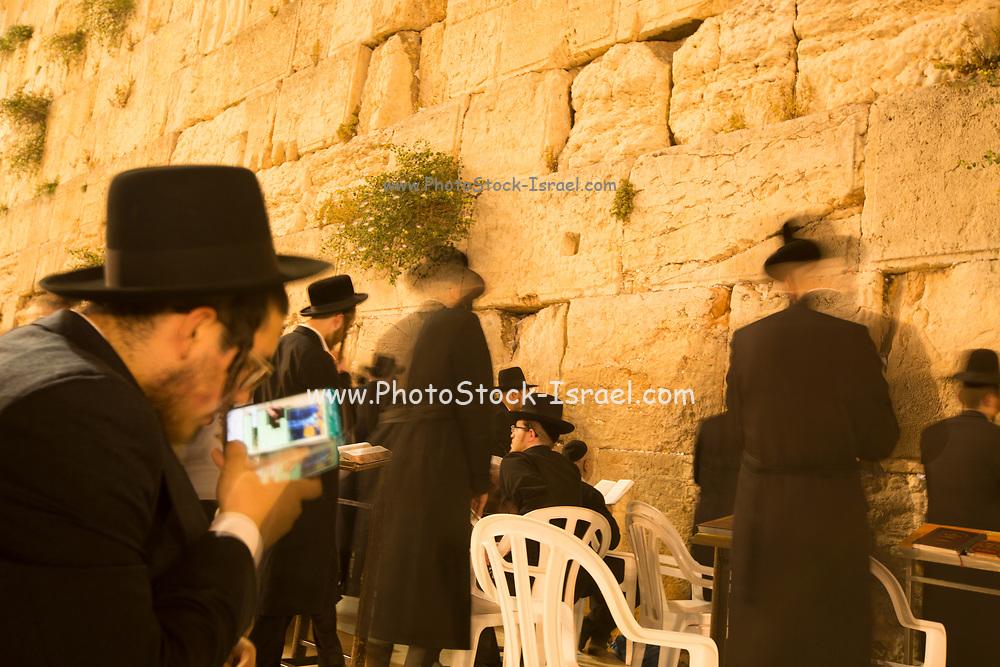 Orthodox Jewish man on his smart phone while praying at the Wailing Wall, Old City, Jerusalem