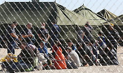 © London News Pictures. Migrants sit in a camp in Roszke, Hungary, September 7 2015. The UN's humanitarian agencies are on the verge of bankruptcy and unable to meet the basic needs of millions of people because of the size of the refugee crisis in the Middle East, Africa and Europe, senior figures within the UN have told the media.   Picture by Paul Hackett /LNP