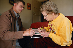 Welfare rights worker helping service user sign forms,