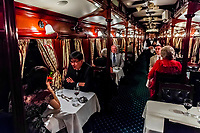 Passengers having dinner in a pillared pre-1940s dining car on the luxury Rovos Rail train between Pretoria and Cape Town, South Africa.